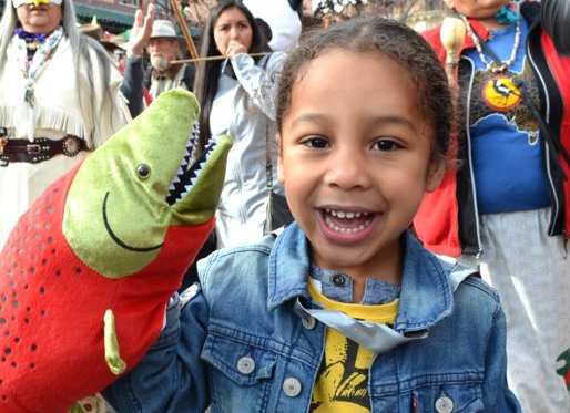 Photo of really cute kid with salmon puppet at Wild Salmon Caravan parade.